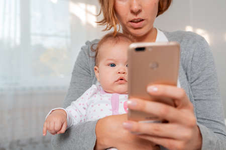Portrait of a baby sitting in the arms of his mother, whose face is covered by a mobile phone. Smartphone is blurred in the foreground.