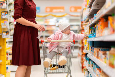 A young mother and her baby sitting in a grocery cart choose baby food on a supermarket shelf. The concept of shopping and parenting.