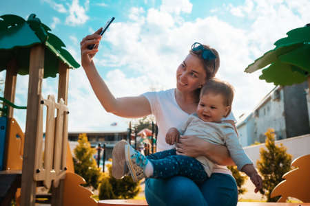 A young happy mother takes a selfie with her baby sitting on her arms. Playground in the background.