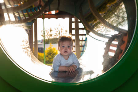 Cute toddler playing on the playground, crawls in a tube. Outdoors. Happy Children's Day.