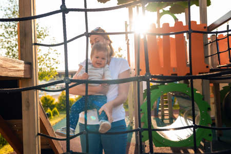 A young caucasian mother plays with a baby on the playground. Sunset in the background. Summertime. 版權商用圖片