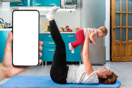 A happy mother holds a baby in her arms while having fun doing fitness together on a mat. A woman's hand on the left side holds a smartphone. Mock up. The concept of home sports training with children.