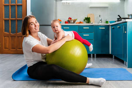 Yoga at home. A young mother leaning on a fit ball and posing with your baby. The concept of fitness with children at home. 版權商用圖片