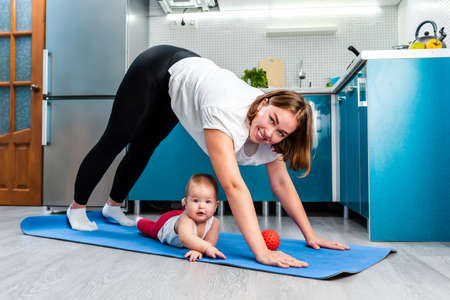 Home yoga. A young Caucasian mother does Adho Mukha Shvanasana while her baby under her on the mat. The concept of sports activity with kids.