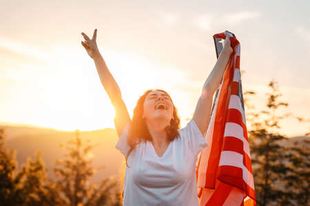 Victory. Happy patriotic young woman has risen an American flag in her hands. Sunset in the background. The concept of American Independence day.