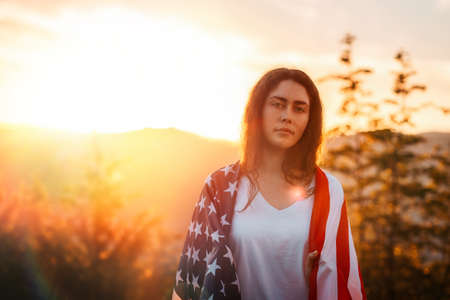Independence day and Memorial Day. Portrait of patriotic young woman with American flag at shoulders. Sunset in the background. Copy space. The concept of American National Holidays.