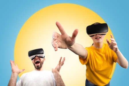 Amazed people wearing virtual reality glasses reach for a virtual object with their hands. Blurred. Blue background with a yellow circle. The concept of virtual reality and modern technologies. 版權商用圖片