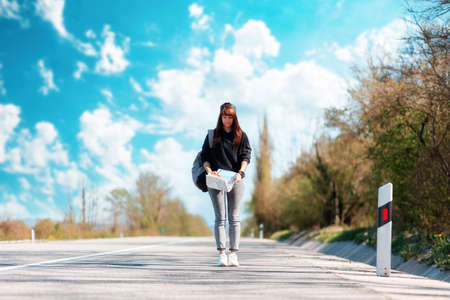 A young woman walks along the road with a map in her hands. Outdoor. Concept of hitchhiking and local travel.