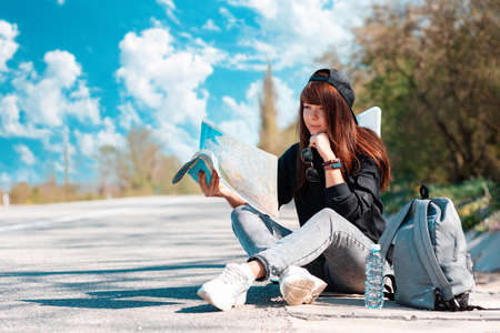 Hitchhiking. Hipster girl in cap sitting along the road and holding a paper map. Copy space. Local travel concept. 版權商用圖片