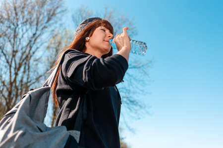 A woman with a backpack drinks water from a bottle. bottom view. The sky is clear in the background. The concept of local hitchhiking. 版權商用圖片