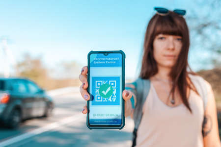 Portrait of a woman holding a smartphone with a negative test results for coronavirus. Digital health passport. The concept of a new normal and travel during the pandemic. 版權商用圖片