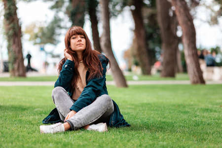 Recreation in the park. Relaxing girl sits cross-legged on the grass. Springtime. Copy space.