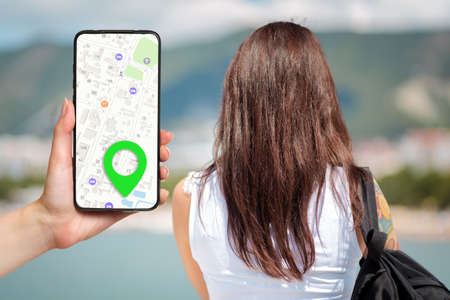 A females hand holds a smartphone with an online map app and a marked destination. In the background, a woman looks at the sea, a view from the back. Concept of online navigation and modern technologies.