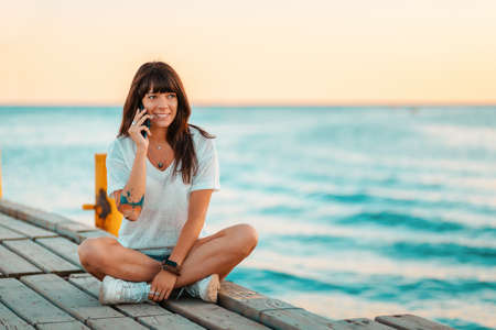 A happy woman with a tattoo on her arm sits on the pier and talks on the phone. Sea in the background. Concept of communication and vacation at the sea.