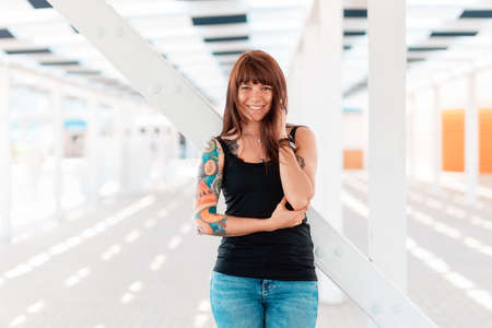 A young happy woman with tattoos on her arm, posing, standing near a white staircase. In the background is an architectural perspective. Outdoor. 版權商用圖片