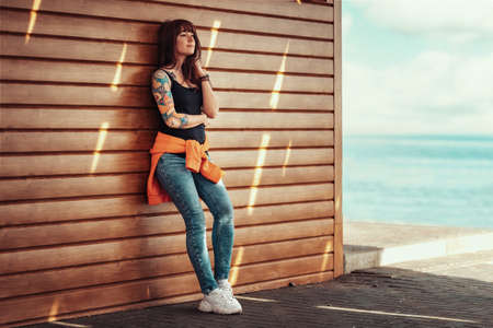 A young beautiful woman with tattoos on her arm, posing near a wooden wall. Sea and beach on the background.