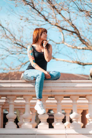 A young smiling woman with tattoed hand sits on the balustrade and looking at the right side. Vertical orientation. Outdoor.