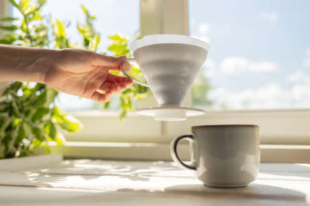 A female's hand removes a funnel with a filter from the cup. Alternative mothod of coffee brewing. Filter V60 with brewed ground coffee. Side view. Window on the background.