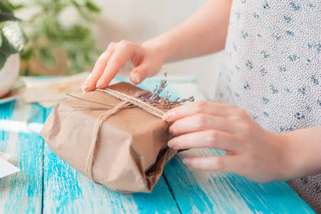 A woman packs a parcel in craft paper wrapped with twine with dried flowers. Hands close-up. Concept of receiving and packing parcels.
