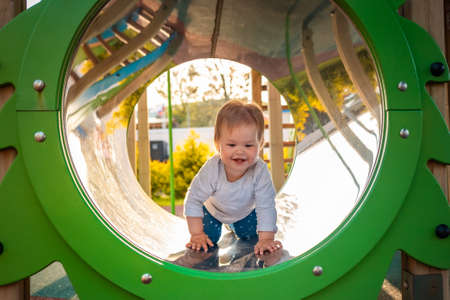 Funny baby playing on the playground, crawls in a tube. Outdoors. Concept of autism.