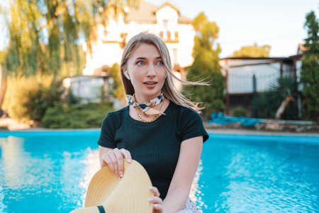 An elegant woman looks away in amazement, holding a hat in her hands. In the background there is a pool and a house. Concept of human emotions and expressions.