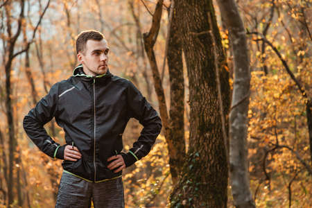 Concept of sport and active lifestyle. A young man in a black tracksuit, posing in the autumn forest. Copy space.