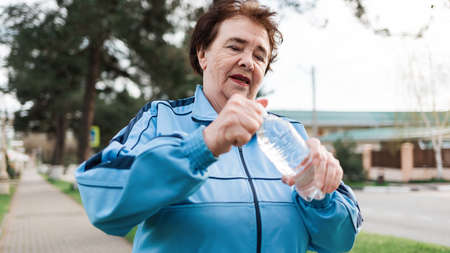 Close up portrait of an elderly smiling woman in a tracksuit opening a bottle of water. Outdoor activity. Concept of International Day of Older Persons.