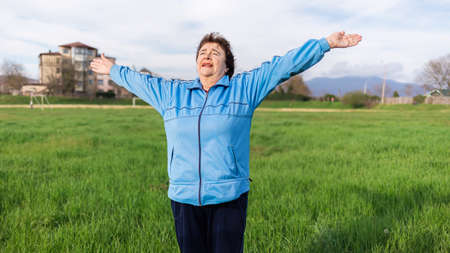 The concept of a healthy lifestyle and sports. Happy elderly woman in sports clothes, doing sports in the park. Grass in the background. International Day of Older Persons. 版權商用圖片