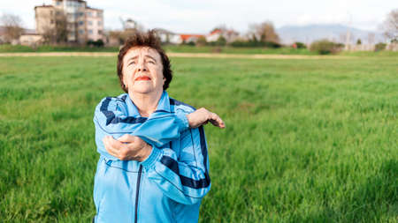 Wellness and sports. Portrait of elderly woman in sports clothes is doing exercises in the park, stretching the joints of her hands. International Day of Older Persons.