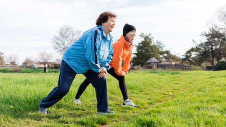 Healthy lifestyle concept. Happy grandmother and granddaughter doing sports together it the park. Old and young women in sports clothes do a stretching. Side view. International Day of Older Persons.