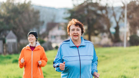 Portraits of the grandmother and granddaughter running together. Mature and young women in sports clothes, jogging in the park. International Day of Older Persons. The concept of a healthy lifestyle.