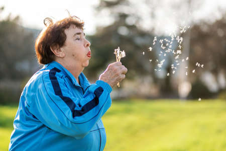 International Day of Older Persons. Portrait of an elderly caucasian grandmother blowing on a dandelion. Park in the background. Copy space. The concept of Alzheimer's disease, dementia.