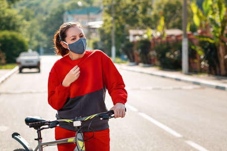 Protection from the virus. Portrait of a woman in a protective medical mask and sportswear, holding a Bicycle, and experiencing fever and shortness of breath. Outdoor. Concept of a viral pandemic.