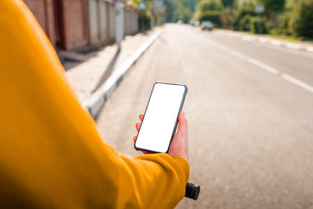 A woman holds a cellphone with an online map app, hand close-up. In the background is a city street. Mock up. The concept of online navigation and modern technologies.