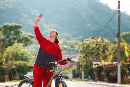 Telecommunication. A young woman in sports clothes, holding a Bicycle and smiling communicates via video link on her phone or takes a selfie. Sunny street on the background.
