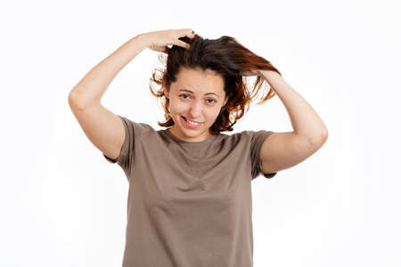 Woman holds her hands to her hair with concern. White background. The concept of hair care. 版權商用圖片