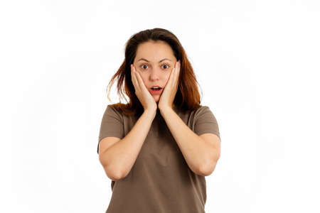 Portrait of a young Caucasian woman clutching her face in fright. White background. The concept of surprise.