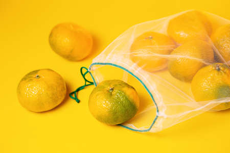 Fresh ripe tangerines in reusable eco friendly mesh bag on yellow background. Top view. Zero waste shopping concept.