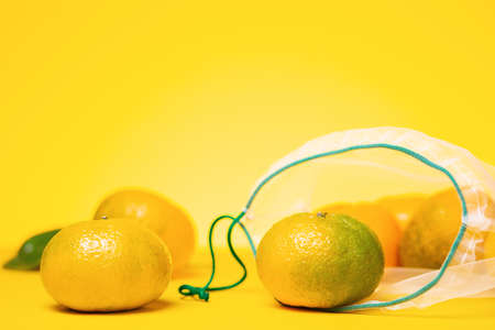 Eco-friendly. Fresh tangerines in reusable eco friendly mesh bag on yellow background. Copy space. Concept of zero waste. Stockfoto