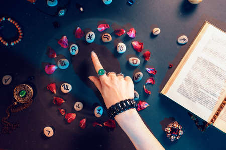 Concept of astrology and horoscope. A woman's hand points to the stones with the signs of the zodiac, laid out in a circle and decorated with rose petals. Divination and magic.