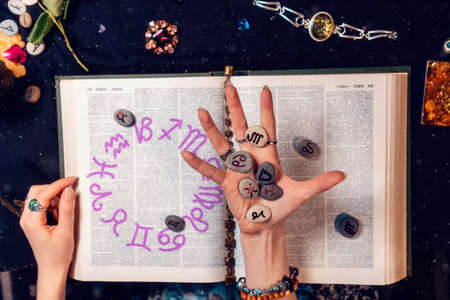 Astrology and horoscope. The fortune teller's hand holds the zodiac stones in the palm of her hand over the open book. Top view, close-up. The concept of divination and magic.