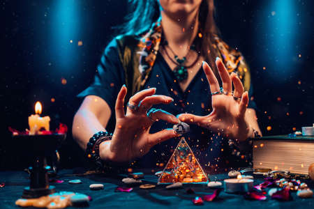 Astrology and horoscope. A witch holds a stone with the sign of the zodiac Libra. Close up. The concept of divination and magic.