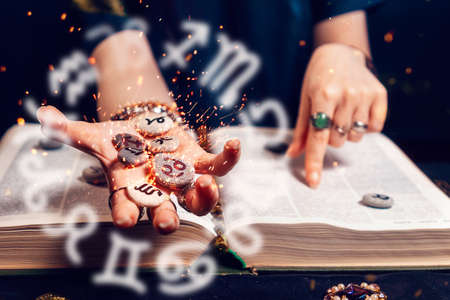 Astrology and horoscope. Fortune teller's hand holds the sparkling zodiac stones in the palm of her hand over the open book. The concept of divination and magic. Stockfoto