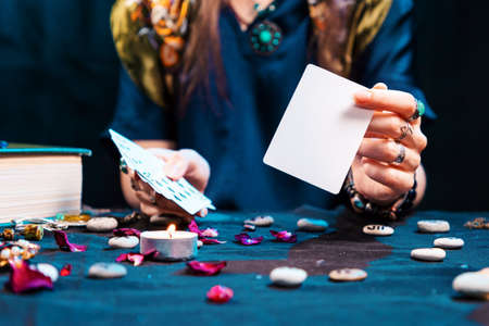 The fortune teller shows an empty white tarot card. Mock up. Copy space. Cartomancy and fortune telling.