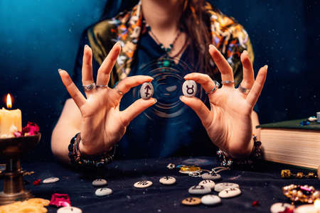 Astrology and horoscope. A woman holds stones with the zodiac sign of Taurus and Sagittarius. The concept of compatibility of partners according to the signs of the zodiac.