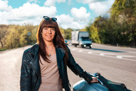 Motorcycle local travel. Portrait of happy young woman in a leather jacket and sunglasses posing near a motorcycle.