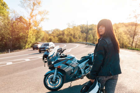 World Motorcyclist Day. A young pretty woman in a leather jacket, holding a motorcycle helmet in her hand. In the background, a motobike and road. Back view. Stockfoto