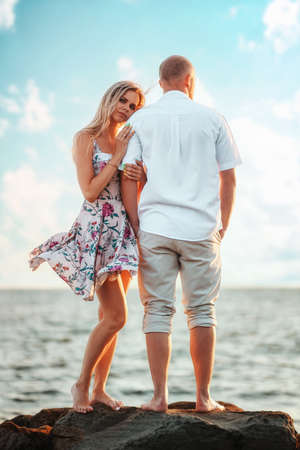 Romantic date. A young couple of Caucasian woman and man are standing on the seashore. Vertical orientation. The concept of Valentine's Day.