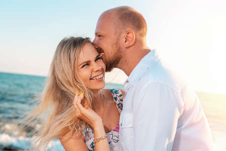A couple of happy young men and women hug and kiss. In the background, the ocean and the sky. Vacation romance concept Stockfoto