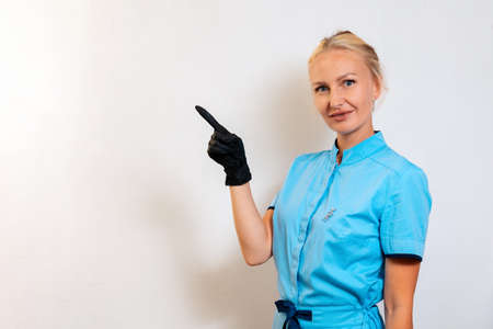 A young woman in a uniform and rubber gloves points her finger to the left. Copy space. Medical worker, cosmetologist and doctor. The concept of business and advertising in the field of medicine and beauty. Stockfoto